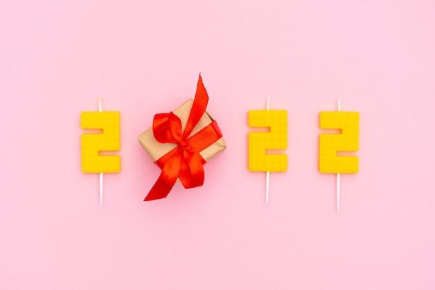 Gelukkig nieuwjaar en kerstviering feestelijke nummerkaarsen kerstcadeaudoos op roze