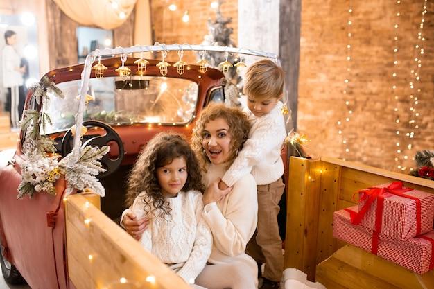 Gelukkig nieuwjaar. glimlachende gelukkige moeder met haar zoon en dochter in rode auto-pick-up