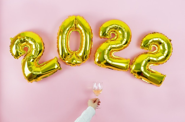 Gelukkig nieuwjaar. hand met witte mouw en beker op roze achtergrond. ruimte kopiëren.