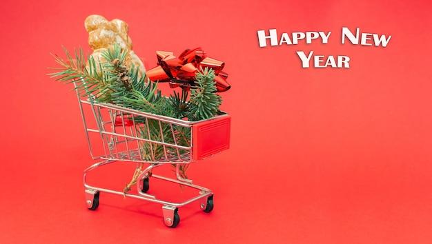 Gelukkig nieuwjaar. kleine winkelwagen met dennentakken, geschenkstrik en gemberbeer.