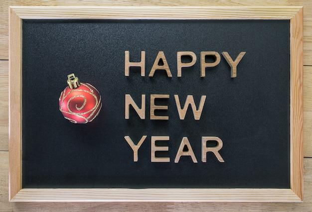 Gelukkig nieuwjaar met houten letters op een houten tafel.