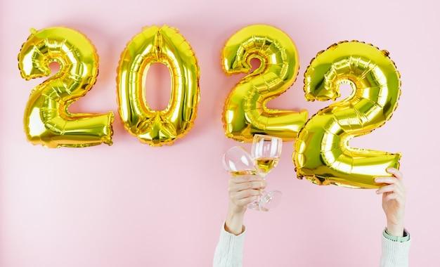 Gelukkig nieuwjaar. nummers 2022. hand met kopjes op roze achtergrond. ruimte kopiëren.