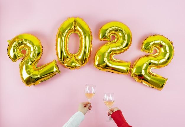 Gelukkig nieuwjaar. nummers 2022. handen met glazen roosteren op roze achtergrond. ruimte kopiëren.