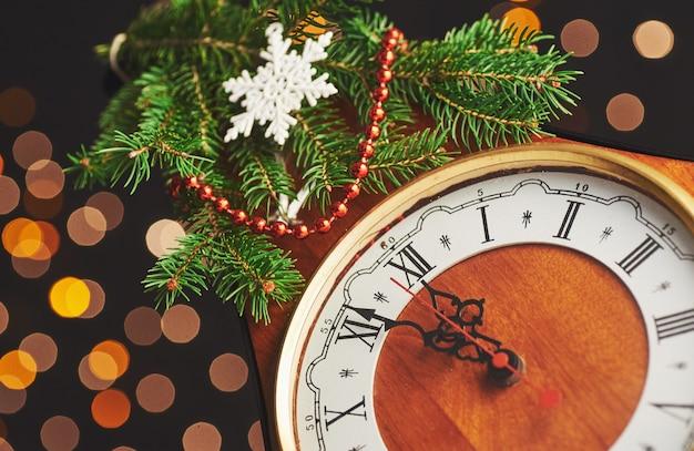 Gelukkig nieuwjaar om middernacht, oude houten klok met vakantielichten en dennentakken