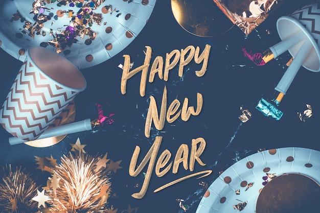 Gelukkig nieuwjaar penseelstreek op tafel met feest beker, feestblazer, klatergoud, confetti