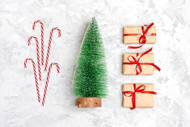 Gelukkig nieuwjaar samenstelling. kerstdecoratiegeschenken, groene boom, snoep, grijs beton