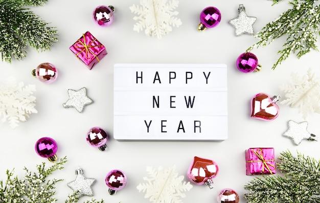 Gelukkig nieuwjaar tekst op lightbox-samenstelling en van kerstmisdecoratie