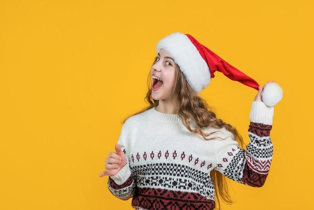 Gelukkig nieuwjaar tienermeisje draagt rode kerstman hoed voelt verrassing, verrassing.