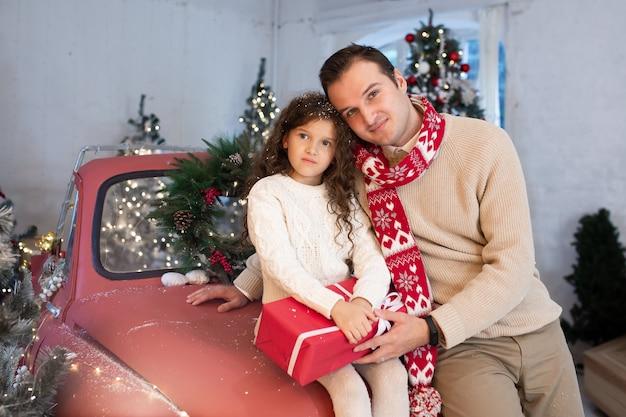 Gelukkig nieuwjaar, vader en dochter met giftdoos dichtbij de kerstboom en rode auto