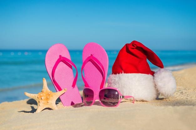 Gelukkig nieuwjaar vakantie en vrolijk kerstfeest op zee. sandalen, zonnebrillen en kerstmuts op zandstrand.