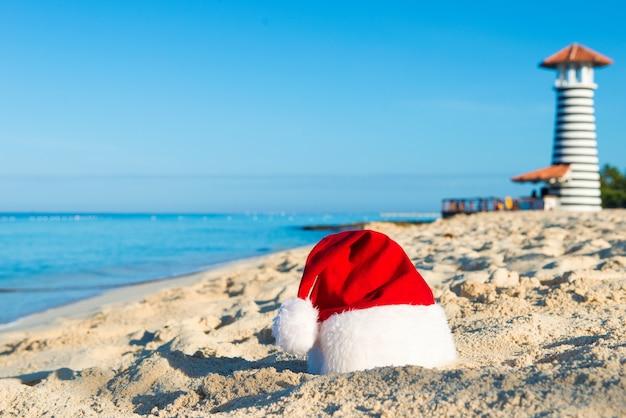 Gelukkig nieuwjaar vakantie op zee. kerstmuts op zandstrand - kerstvakantie concept