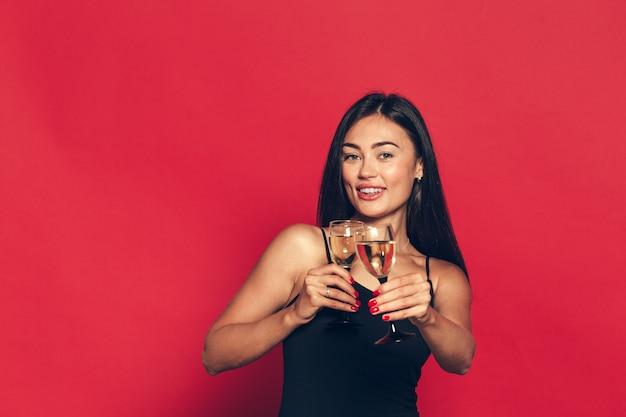 Gelukkig nieuwjaar voor jou. een jonge en mooie vrouw dansen met glas champagne