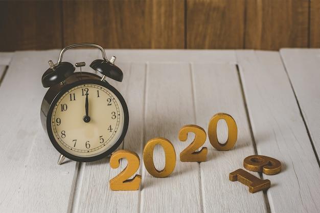 Gelukkig nieuwjaarconcept met wekker en houten gouden nummer 2020