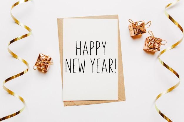 Gelukkig nieuwjaarsbriefje met envelop, geschenken en gouden lint op witte achtergrond. vrolijk kerstfeest en nieuwjaarsconcept
