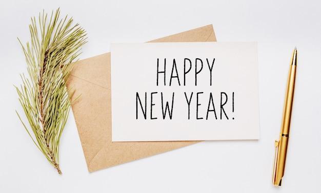 Gelukkig nieuwjaarsbriefje met envelop, vuren tak en gouden pen op witte achtergrond. vrolijk kerstfeest en nieuwjaarsconcept