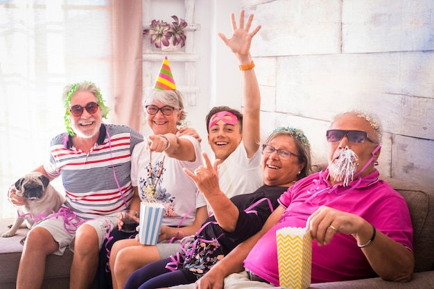 Gelukkig nieuwjaarsfeest thuis met jonge en oudere mensen die allemaal samen plezier hebben en op de camera kijken - vrolijke gemengde generaties mensen genieten van een feestje binnen