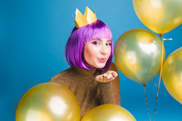 Gelukkig nieuwjaarsfeest van aantrekkelijke jonge vrouw die een kus verzendt, omringt gouden ballons. paars haar knippen, luxe kleding, plezier maken, verjaardagsfeestje.