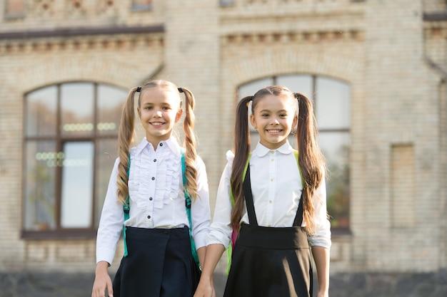Gelukkig om elkaar te ontmoeten. vrolijke slimme schoolmeisjes. gelukkig schoolmeisjes buitenshuis. kleine schoolmeisjes dragen schooluniform. schattige schoolmeisjes met lange paardenstaarten zien er charmant uit. einde schooljaar.