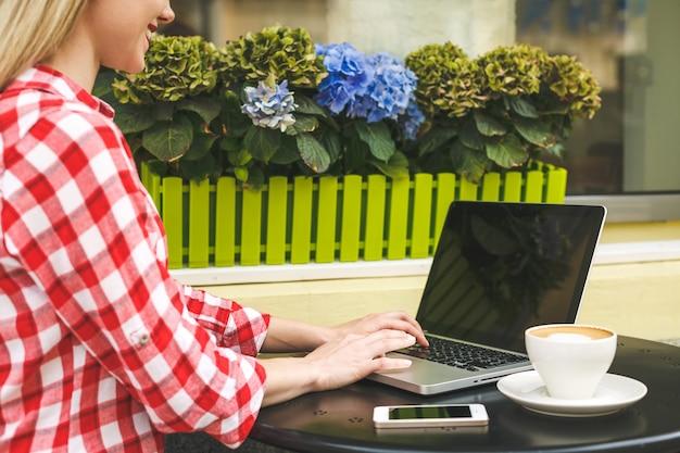 Gelukkig ondernemer werken met een telefoon en laptop in een koffieshop in de straat. close-up concept.