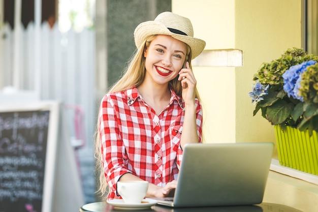 Gelukkig ondernemer werken met een telefoon en laptop in een koffieshop in de straat