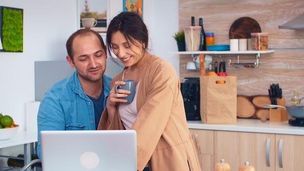 Gelukkig ondernemerspaar dat 's ochtends op laptop in de keuken werkt. man en vrouw koken recept eten. gelukkig gezond samen levensstijl. familie op zoek naar online maaltijd. gezondheid frisse salade