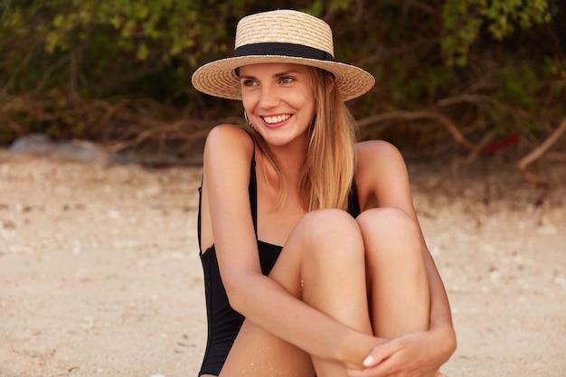Gelukkig ontspannen jonge mooie vrouw in strohoed, houdt benen gebogen in knieën zoals zit op warme zomer zandstrand, kijkt weg met dromerige en positieve uitdrukking