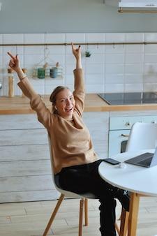 Gelukkig ontspannen jonge vrouw zitten in haar keuken met een laptop voor haar strekken haar armen boven haar hoofd en kijkt uit het raam met een glimlach