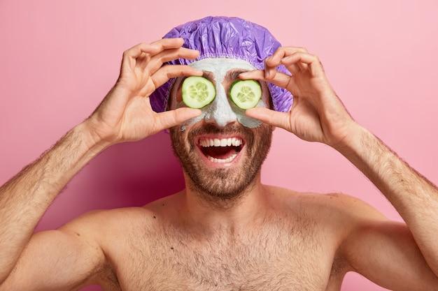Gelukkig ontspannen jongeman bedekt ogen met twee plakjes komkommer, brengt een cosmetisch masker op het gezicht aan, draagt een badmuts, staat naakt tegen een roze muur. zelfzorg, schoonheid en spa-therapie concept