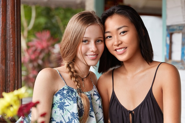 Gelukkig ontspannen mooie twee jonge vrouwtjes genieten van saamhorigheid, vrije tijd doorbrengen in oosterse café, poseren voor de camera met opgetogen uitdrukkingen.
