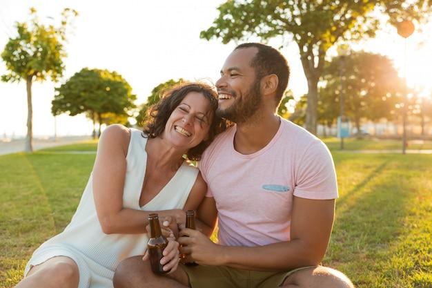 Gelukkig ontspannen paar dat en van zonsondergang lacht geniet