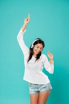 Gelukkig ontspannen vrouw in koptelefoon dansen en luisteren naar muziek