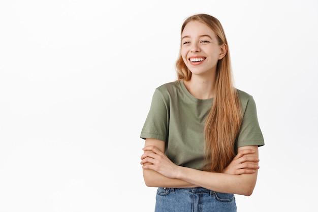 Gelukkig openhartig meisje dat lacht en glimlacht, opzij kijkt naar het advertentielogo met een blij gezicht, staat alsof ze een informeel ontspannen gesprek heeft met vrienden, witte muur