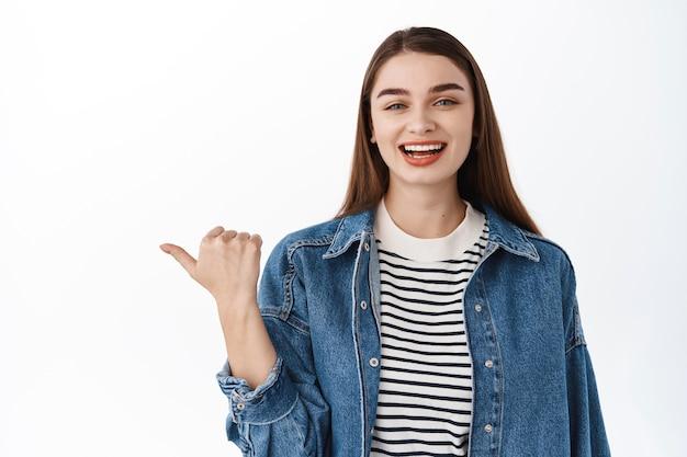 Gelukkig openhartig meisje in denim zomerjas, opzij wijzend, lachend en glimlachend blij, met promotionele banner, tekst op kopieerruimte of logo, staande over witte muur