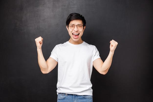 Gelukkig opgelucht en tevreden jonge aziatische man feliciteert zijn team met winst, behaalt doel, balt handen als kampioen, viert succes zeggend ja, zegevierend over overwinning, zwarte muur