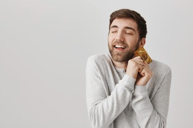 Gelukkig opgetogen bebaarde man knuffelen koude creditcard
