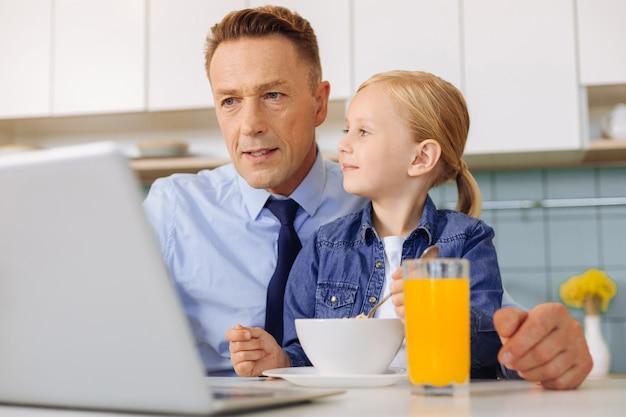 Gelukkig opgetogen schattig meisje kijkt naar haar vader en lacht terwijl ze in een goed humeur is