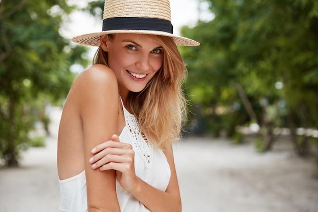 Gelukkig opgetogen vrouw heeft een aangename, aantrekkelijke uitstraling, draagt een zomerhoed en een witte jurk, wandelt op straat, geniet van vakanties of vrije dagen. vrij jong groenogig blij vrouwelijk model stelt openlucht