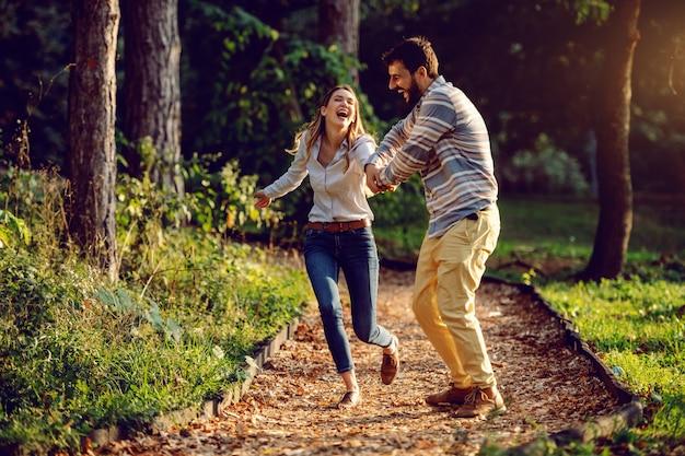 Gelukkig opgewekt kaukasisch jong paar dat op sleep in hout loopt en goede tijd heeft. man die de hand van de vrouw houdt. avontuur in de natuur concept.
