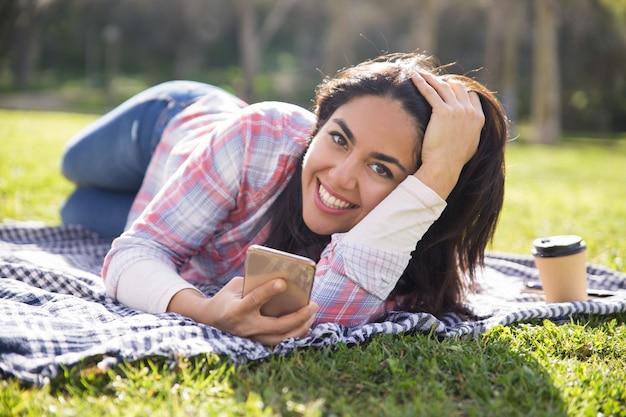 Gelukkig opgewekt studentenmeisje die in park rusten en berichten verzenden