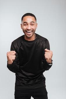 Gelukkig opgewonden afro-amerikaanse jonge man permanent en vieren van succes