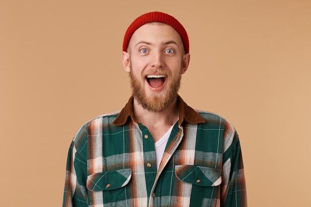 Gelukkig opgewonden bebaarde man in rode hoed geïsoleerd over beige muur