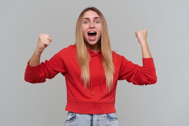 Gelukkig opgewonden blonde jonge vrouw met sproeten in rode hoodie houdt handen en vuisten opgeheven en schreeuwen over grijze muur vieren overwinning