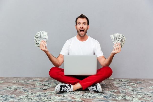 Gelukkig opgewonden casual man zittend op de vloer met laptop en geld aanhouden over grijze achtergrond