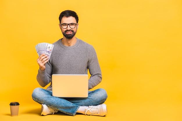Gelukkig opgewonden casual man zittend op de vloer met laptop en geld geïsoleerd op gele achtergrond te houden.