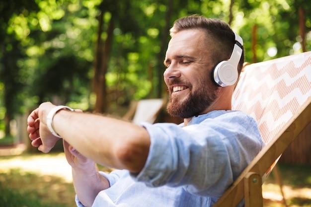 Gelukkig opgewonden emotionele jonge bebaarde man luisteren muziek met koptelefoon.