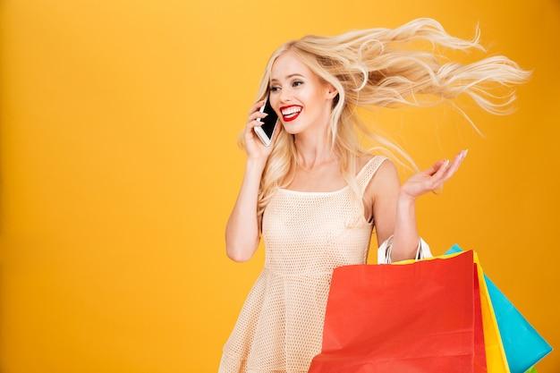Gelukkig opgewonden geweldige jonge blonde vrouw praten via de telefoon.
