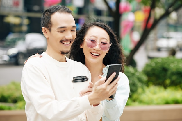 Gelukkig opgewonden jong chinees stel met afhaalkoffie die selfie op smartphone neemt wanneer ze buiten staan