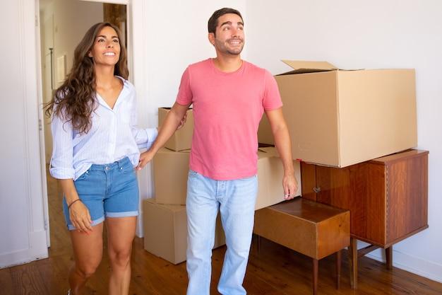 Gelukkig opgewonden jong koppel kijkt uit over hun nieuwe appartement met kartonnen dozen en meubels, glimlachend en praten