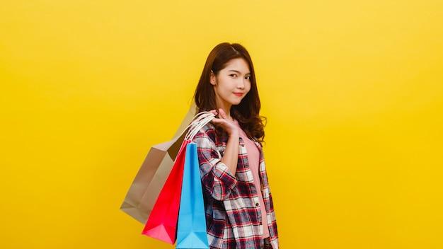 Gelukkig opgewonden jonge aziatische dame met boodschappentassen met hand verhogen in casual kleding en camera kijken op gele muur. gelaatsuitdrukking, seizoensgebonden verkoop en consumentisme concept.