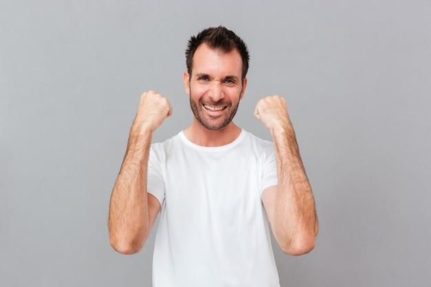 Gelukkig opgewonden jonge casual man viert succes over grijze achtergrond